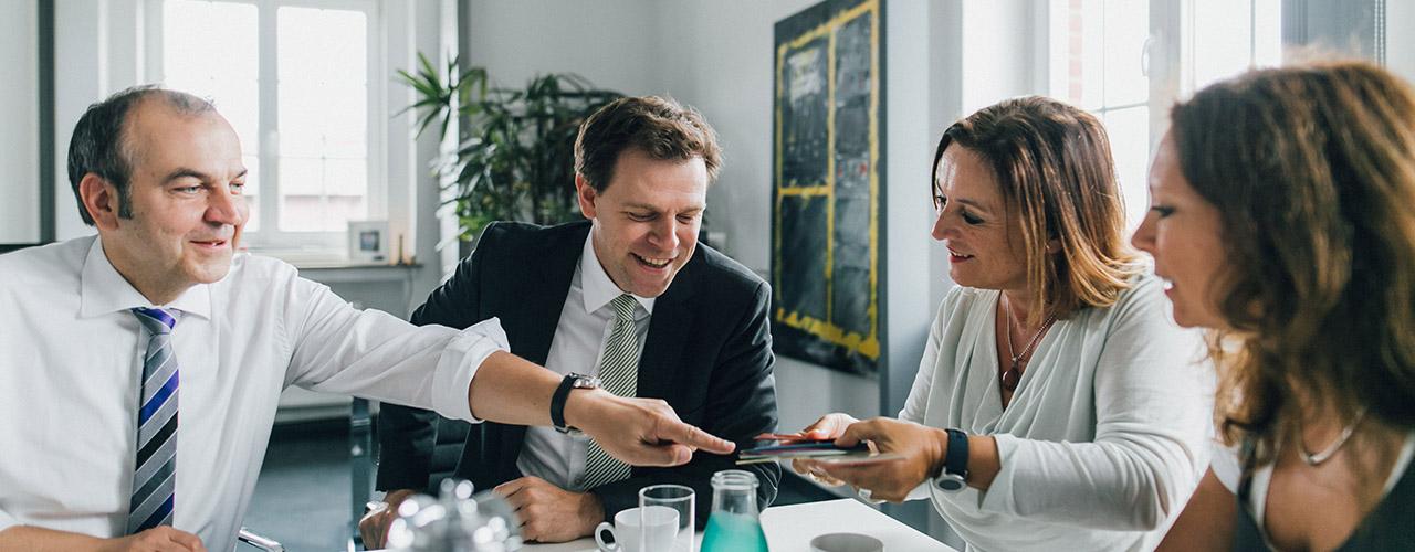 Krefelder Netzwerk Wirtschaft & Familie, Kategorie Service für Unternehmen.Titelbild. Vier Personen, zwei Männer und zwei Frauen, sitzen am Besprechungstisch und sind ein Gespräch verwickelt. Copyright Matthias Heuser, neu-artig.com