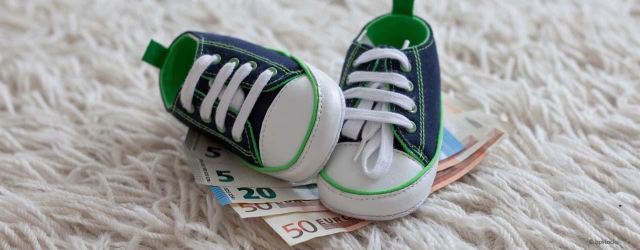 Kinderbetreuungszuschuss. blaue-grüne Baby-Sneaker stehen auf einem Geldfächer aus 5, 20 und 50 Euro. Copyright © bpstocks