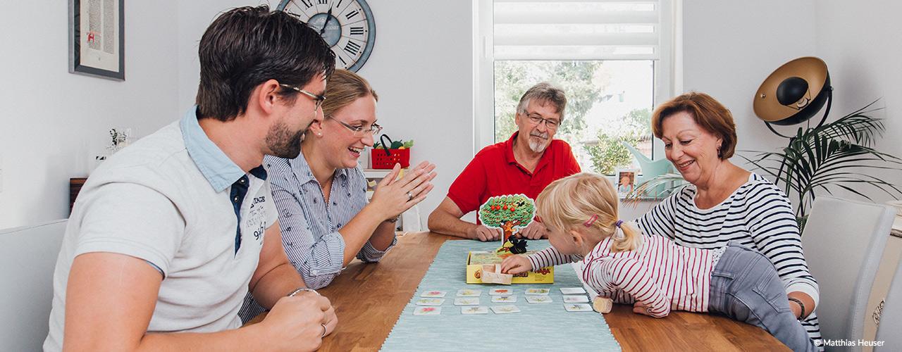 Familie (Großeltern, Eltern und Kind) spielen ein Spiel am Esstisch. Copyright: Matthias Heuser, neu-artig.com