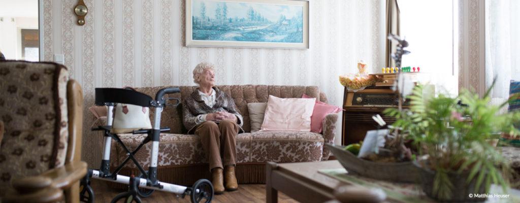 Ältere Dame sitzt in ihrem Wohnzimmer auf dem Sofa und schaut verträumt. Copyright: Matthias Heuser - neuartig.com